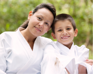 Woman and child smiling in Taekwondo garb