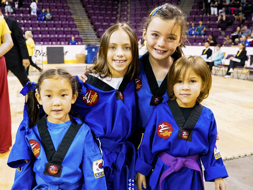 Four child students smiling dressed in blue taekwondo garb