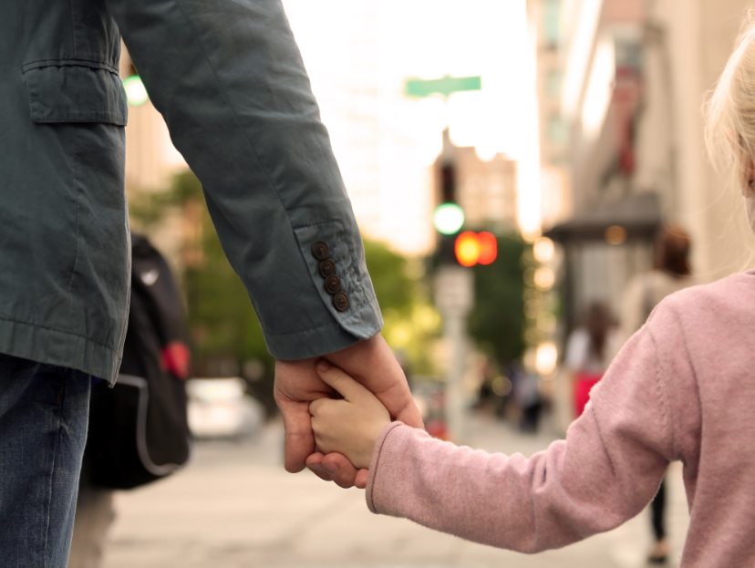 Child holding her father's hand