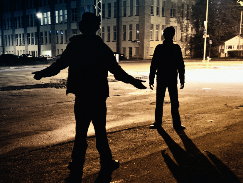 Two silhouettes of men in a dark alley